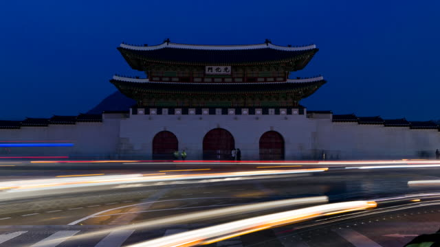 TL Rush hour traffic and pedestrians speed past Gwanghwamun Gate at Gyeongbokgung Palace / Seoul, South Korea