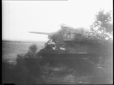 Russian military courier arrives at headquarters / Russian soldier looks at watch / troops and tanks from behind trees and advance across fields on...