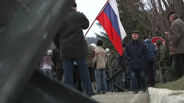 Russian militia surround a Ukrainian military base in Privolnoye Shows pro Russia militia soldiers armed and standing around outside military base...