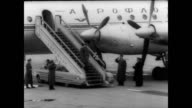 / CU of Russian plane arriving at airport / huge crowd with signs depicting Russian astronaut Yuri Gagarin / Gagarin walks confidently off plane to...
