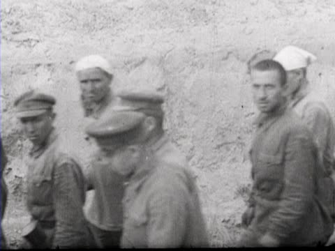 Russian prisoners of war run over a pontoon bridge and then walk past German soldiers