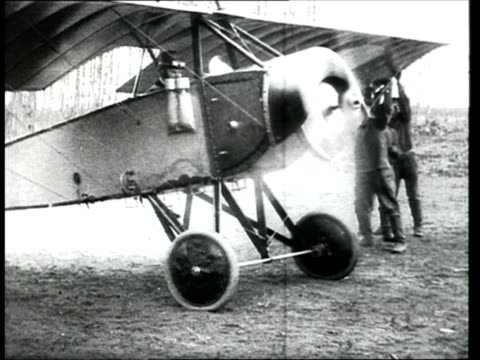 1915 MONTAGE B/W MS Russian soldier spinning propeller on military plane before takeoff/ WS Plane taking off from airfield/ Russia