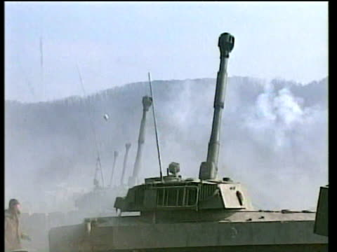 Russian tanks fire at suspected rebel positions in the mountains south of Grozny plumes of smoke rise on the horizon 18 Feb 00