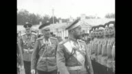 Russian Tzar of Russia Nicholas II revues a line of troops accompanied by bemedaled officers
