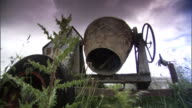 Rusted portable cement mixer w/ mouth aimed downward in farm yard next to tractor tire tall thistle plant overgrown grass Older equipment selfreliant...