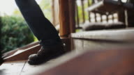 Rustic porch steps; a man in work boots and blue jeans walk though frame, going to work.
