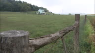 A rustic wooden fence surrounds a grassy field next to a farmhouse.