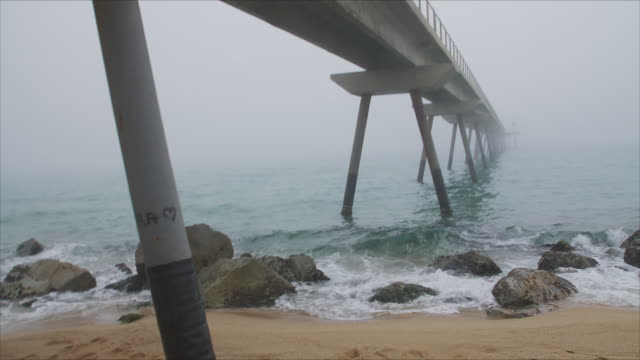 Rusty bridge goes from the shore to the sea and the fog. Seen from the point of view of a person that is walking on a lonely beach.