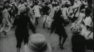 1930's B/W MONTAGE British police beating people on streets of Indian town / India