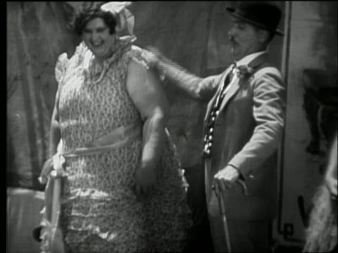 B/W 1920's carnival side show barker on stage with fat lady and hula dancer