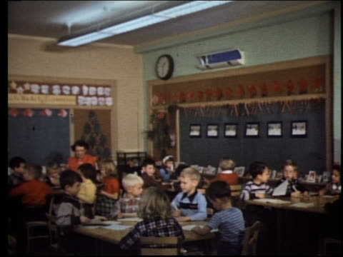 1960's children and teacher working at tables in classroom