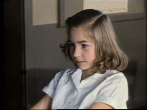 1960's close up of girl at desk turning to talk to someone behind her / Classroom