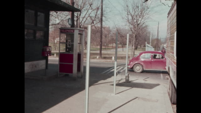1960's image of inner city store in Nashville showing black woman walking toward the store and going inside view of Volkswagen 'beetle' driving by