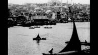1930's Istanbul skyline Sultanahmet district from the Golden Horn dhows sailing by Rüstem Pasha and Süleymaniye mosques visable / Karakoy district...