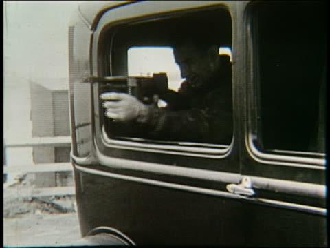 B/W 1920's man shooting machine gun from car window