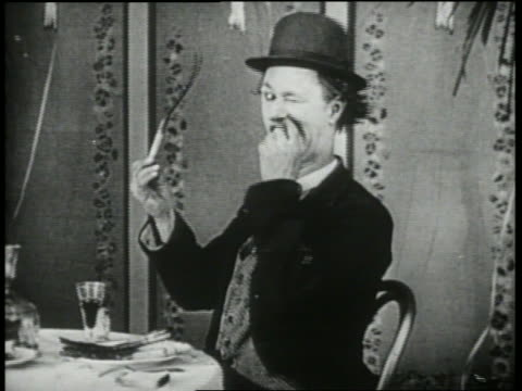 B/W 1920's man (Ben Turpin) trying to eat twisting, bending piece of asparagus