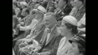 MS US's Shirley Fry picks up tennis racket from tennis court at Wimbledon for match against US's Doris Hart / CU crowd watches match / VS crowd...