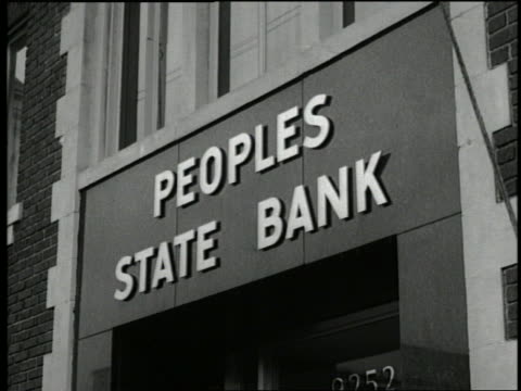 B/W 1940's tilt down from sign to 2 men walking out of bank