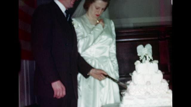 1940's Wedding - Newlyweds cut cake at wedding reception