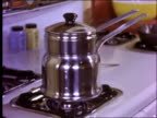 1950's zoom out of woman stirring pot on stove and opening oven to check on food