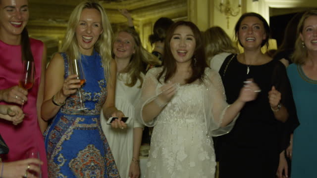 Sabrina Ho dances on chair with guests at her birthday party at Oscar Wilde Bar Hotel Cafe Royal on September 12 2016 in London England