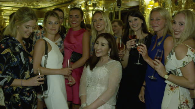 Sabrina Ho poses for photos with guests at her birthday party at Oscar Wilde Bar Hotel Cafe Royal on September 12 2016 in London England