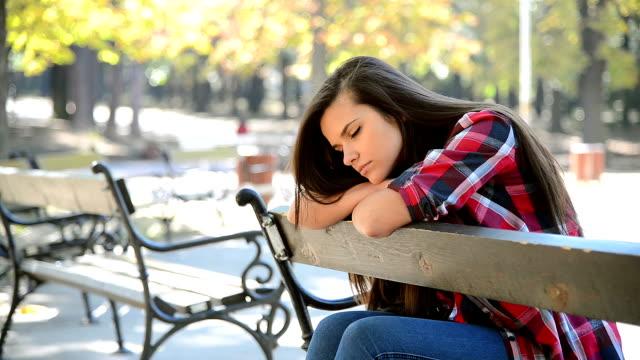 Verdrietig meisje zittend op een bankje