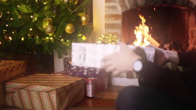 DS MS traurig aussehender junger Mann hält ein Weihnachtsgeschenk