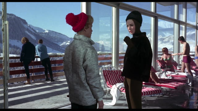 Sad woman (Audrey Hepburn) discusses impending divorce with friend as they stroll through an alpine resort