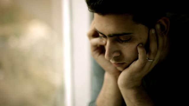 Trauriger junger Mann hielt seinen Kopf und denken in der Nähe von Fenster.