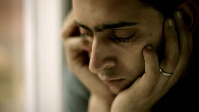 Sorgsen ung man håller hans huvud och tänka nära fönstret.