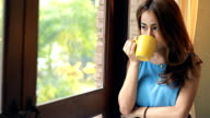Sad young woman drinking coffee at home
