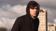 Sad youth / Hoody on council estate with flats behind