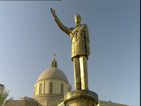 Saddam Hussein golden statue with mosque dome in background / Baghdad Iraq