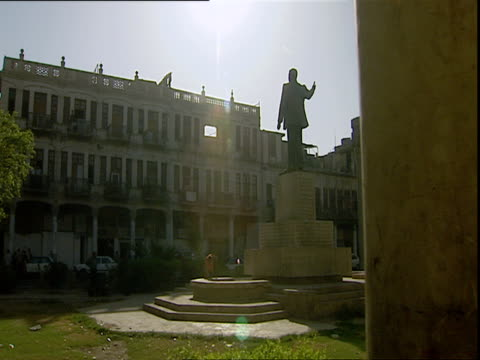 Saddam Hussein statue with street and buildings in background / Baghdad Iraq