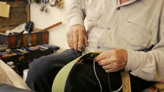 Saddler. Saddle manufacture. Leather goods craftsman at work in his workshop.