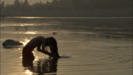 Sadhu washes hair in River Ganges flicking his hair back, Rishikesh Available in HD.