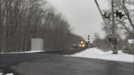 A safety barricade drops at a railroad crossing as a train travels past in the snow.