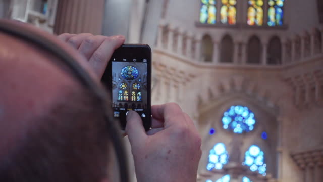 Sagrada Familia, tourist taking photo with a phone indoors. Barcelona cathedral by Gaudi. Ceiling, columns and colorful stained glass windows. Wolrd famous artistical architecture from Modernism in Catalonia.