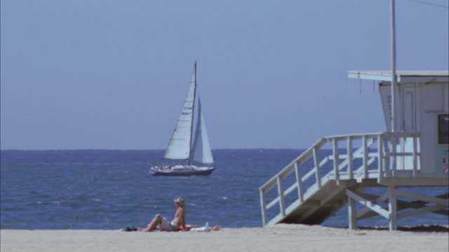 TS Sailboat in the ocean sailing and sun-bathers laying out by the lifeguard station on the beach / Santa Monica, California, United States