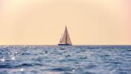 SLO MO Sailboat sailing on the horizon at sunset