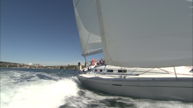 A sailboat sails near the wake of another boat in Sydney Harbour