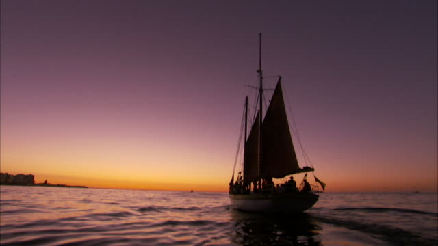 A sailboat travels towards the sunset. Available in HD
