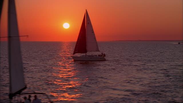 LOW AERIAL, Sailboats in Tampa Bay at sunset, Florida, USA