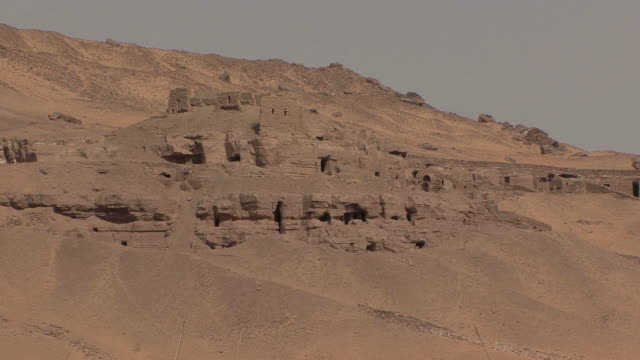 POV Sailing on Nile by ancient tombs of nobles carved in mountain in Roman times, Aswan, Egypt