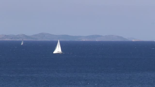 Sailing right to left in front of land mass in distance Off the coast of Croatia near Primosten Shot from 'Villa Welles'