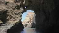POV Sailing through rocky caves and cliffs at Praia Dona Ana, Atlantic Ocean coast / Portugal