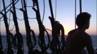 Sailor and ropes silhouetted on board replica of HMS Endeavour by setting sun.