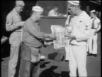 B/W 1945 sailor buying VJDay newspaper from second sailor selling outdoors