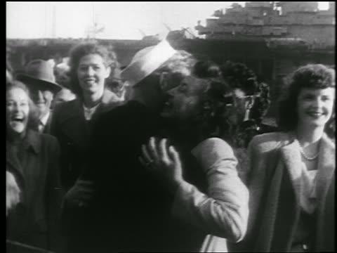 B/W 1945 sailor hugs 2 women / end of WWII / educational